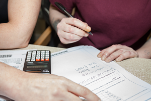 Stock photograph of two women with books and a calculator